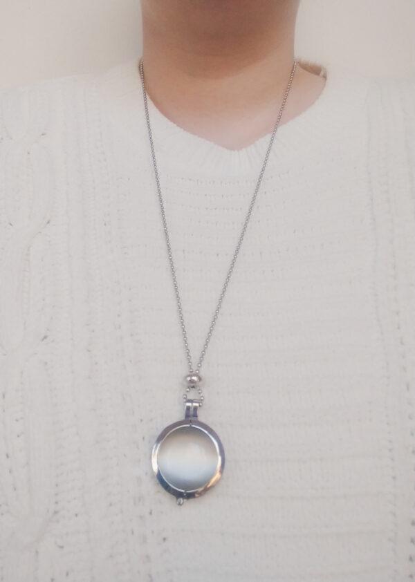 Ketting cateye wit. Dubbelzijdige cateye steen in hanger aan een bolletjes ketting. De steen heeft 2 kanten, 1 met een cateye en 1 met kleine steentjes in een witte kleur. De ketting wordt getoond om de net van een blanke vrouw met een witte gebreide trui.