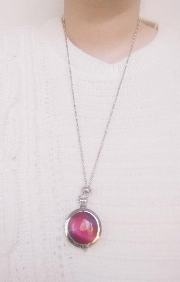 Ketting cateye roze. Dubbelzijdige cateye steen in hanger aan een bolletjes ketting. De steen heeft 2 kanten, 1 met een cateye en 1 met kleine steentjes in een grijze/zwarte kleur. De ketting wordt getoond om de net van een blanke vrouw met een witte gebreide trui.