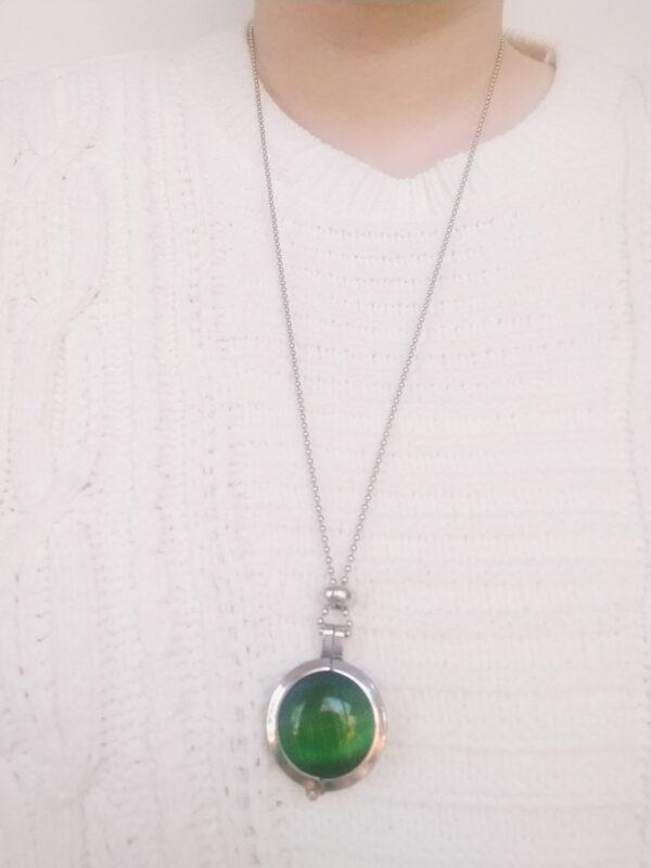 Ketting cateye groen. Dubbelzijdige cateye steen in hanger aan een bolletjes ketting. De steen heeft 2 kanten, 1 met een cateye en 1 met kleine steentjes in een grijze/zwarte kleur. De ketting wordt getoond om de net van een blanke vrouw met een witte gebreide trui.