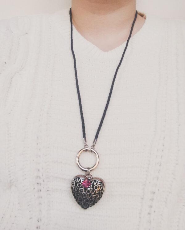 """Ketting grijs leer clip-ring hart swarovski roze. Grijze gevlochten leren ketting met een metalen clip-ring met een bedel van een hart met het woord """"LOVE"""" erop. Er hangt een swarovski kraal aan in de kleur rose, een roze kleur. De leren ketting is 76 cm lang. De ketting wordt getoond om de hals van een blanke vrouw met een witte gebreide trui aan."""