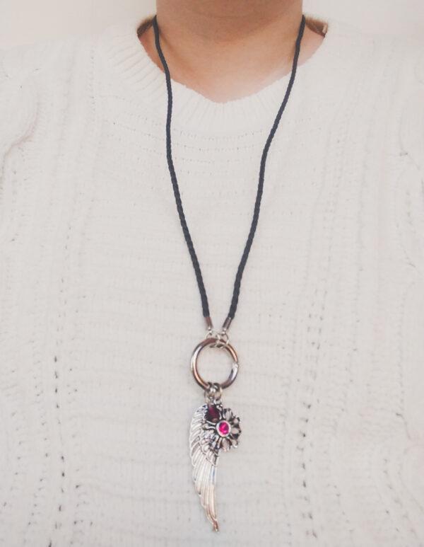 Ketting grijs leer clip-ring vleugel swarovski donker roze. Grijze gevlochten leren ketting met een metalen clip-ring met een bedel van een vleugel en een bloem met een swarovski steentje. Er hangt een swarovski kraal aan in de kleur fuchsia, een donker roze kleur. De leren ketting is 76 cm lang. De ketting wordt getoond om de hals van een blanke vrouw met een witte gebreide trui aan.