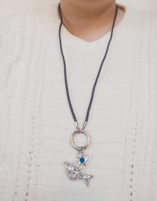 Ketting grijs leer clip-ring vogel swarovski blauw. Grijze gevlochten leren ketting met een metalen clip-ring met een bedel van een vogel. Er hangt een swarovski kraal aan in de kleur capri blue, een blauwe kleur. De leren ketting is 76 cm lang. De ketting wordt getoond om de hals van een blanke vrouw met een witte gebreide trui aan.