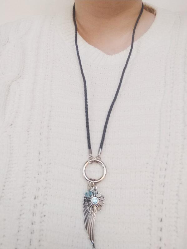 Ketting zwart leer clip-ring vleugel swarovski licht blauw. Zwarte gevlochten leren ketting met een metalen clip-ring met een swarovski kraal in de kleur aquamarine, een licht blauwe kleur en een bedel van een vleugel en een bloem met een swarovski steentje. De leren ketting is 76 cm lang. De ketting wordt getoond om de hals van een blanke vrouw met een witte gebreide trui aan.