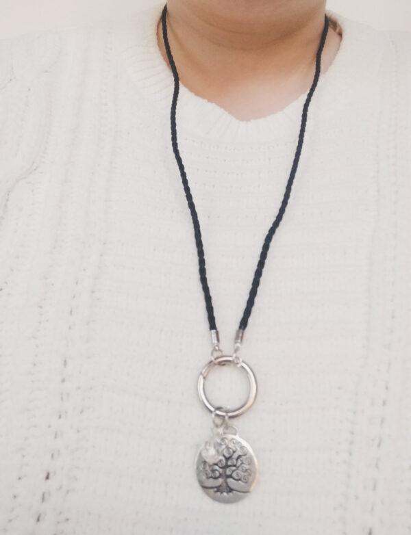 Ketting zwart leer clip-ring tree of life swarovski kristal. Zwarte gevlochten leren ketting met een metalen clip-ring met een bedel van eenboom met een kristal swarovski kraal. De leren ketting is 76 cm lang. De ketting wordt getoond om de hals van een blanke vrouw met een witte gebreide trui aan.