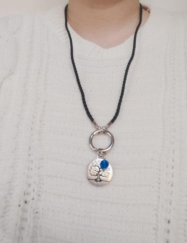 Ketting zwart leer clip-ring tree of life swarovski blauw. Zwarte gevlochten leren ketting met een metalen clip-ring met een bedel van een boom met een blauwe swarovski kraal. De leren ketting is 76 cm lang. De ketting wordt getoond om de hals van een blanke vrouw met een witte gebreide trui aan.