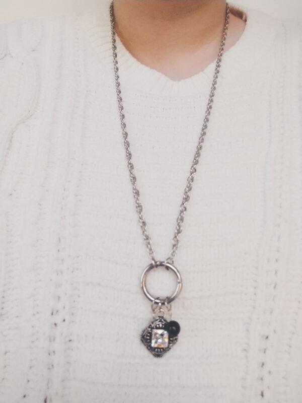 Ketting clip-ring romantic square swarovski kristal. Metalen schakelketting met een metalen clip-ring met bedel van een metalen hanger romantic square, een vierkante hanger met een vierkante swarovski steen in de kleur cyrstal, een kristal kleur. Er hangen ook nog een zwarte swarovski parel en een swarovski kraal in de kleur crystal, een kristal kleur. De schakel ketting is 60 cm lang. De ketting wordt getoond om de hals van een blanke vrouw met een witte gebreide trui aan.