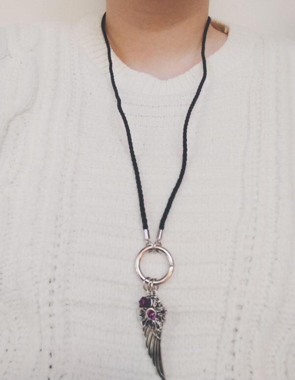 Ketting zwart leer clip-ring vleugel swarovski paars. Zwarte gevlochten leren ketting met een metalen clip-ring met een swarovski kraal in de kleur amethyst, een paarse kleur en een bedel van een vleugel en een bloem met een swarovski steentje. De leren ketting is 76 cm lang. De ketting wordt getoond om de hals van een blanke vrouw met een witte gebreide trui aan.
