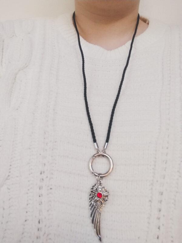 Ketting zwart leer clip-ring vleugel swarovski rood. Zwarte gevlochten leren ketting met een metalen clip-ring met een bedel van een vleugel en een bloem met een swarovski steentje in de kleur siam, een rode kleur. De leren ketting is 76 cm lang. De ketting wordt getoond om de hals van een blanke vrouw met een witte gebreide trui aan.