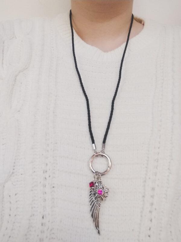 Ketting zwart leer clip-ring vleugel swarovski donker roze. Zwarte gevlochten leren ketting met een metalen clip-ring met een swarovski kraal in de kleur fuchsia, een donker roze kleur en een bedel van een vleugel en een bloem met een swarovski steentje. De leren ketting is 76 cm lang. De ketting wordt getoond om de hals van een blanke vrouw met een witte gebreide trui aan.