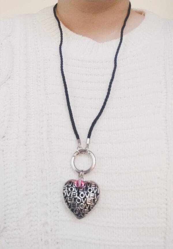 """Ketting zwart leer clip-ring hart swarovski roze. Zwarte gevlochten leren ketting met een metalen clip-ring met een bedel van een hart met het woord """"Love"""" erop. Er hangt een swarovski kraal aan in de kleur rose, een roze kleur. De leren ketting is 76 cm lang. De ketting wordt getoond om de hals van een blanke vrouw met een witte gebreide trui aan."""