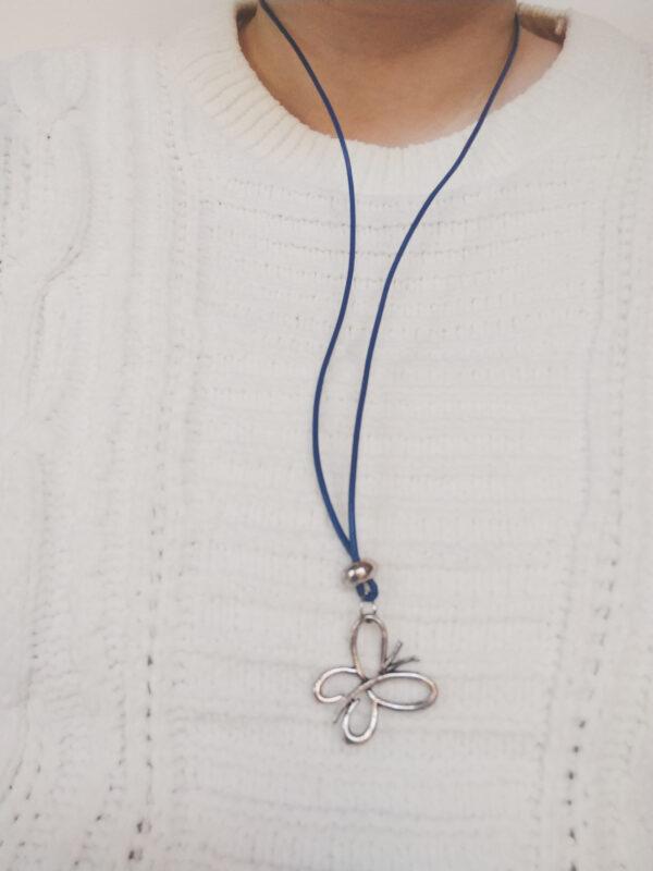 Ketting blauw leer vlinder. Een dun blauw leren ketting met een metalen kraal met daaronder een vlinder bedel. Het kettinkje is 80 cm lang. De ketting wordt getoond om de hals van een blanke vrouw met een witte gebreide trui aan.