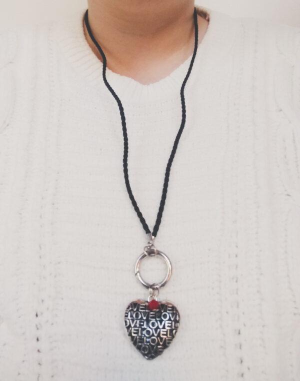 """Ketting zwart leer clip-ring hart glas rood. Zwarte gevlochten leren ketting met een metalen clip-ring met een hart met het woord """"love"""" erop. Met een facet geslepen rond rood glas kraaltje. De leren ketting is 76 cm lang. De ketting wordt getoond om de hals van een blanke vrouw met een witte gebreide trui aan."""