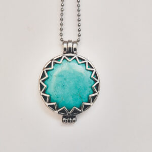Ketting turquoise. Metalen medaillon met kleine driehoekjes rond de rand met een natuursteen turquoise erin, aan een bolletjesketting. De steen kan worden verwisseld met andere kleuren. De bolletjes ketting is 80 cm lang.