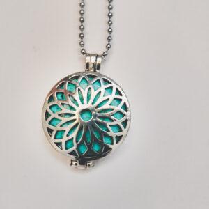 Ketting bloem medaillon turquoise. Metalen medaillon met een turquoise natuursteen erin, aan een bolletjesketting. De steen kan worden verwisseld met andere kleuren. De bolletjes ketting is 68 cm lang.