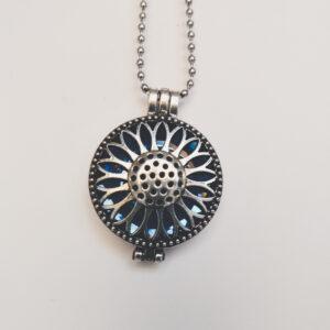Ketting zonnebloem medaillon blauw. Metalen zonnebloembloem medaillon met een blauwe steen erin, aan een bolletjesketting. De steen kan worden verwisseld met andere kleuren. De bolletjes ketting is 68 cm lang.