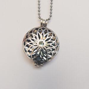 Ketting bloem medaillon grijs. Metalen bloem medaillon met een grijze steen erin, aan een bolletjesketting. De steen kan worden verwisseld met andere kleuren. De bolletjes ketting is 68 cm lang.