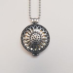 Ketting zonnebloem medaillon kristal. Metalen zonnebloembloem medaillon met een kristal steen erin, aan een bolletjesketting. De steen kan worden verwisseld met andere kleuren. De bolletjes ketting is 68 cm lang.