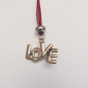Ketting rood leer love. Een dun rood leren ketting met een metalen kraal met daaronder een Love bedel. Het kettinkje is 80 cm lang.