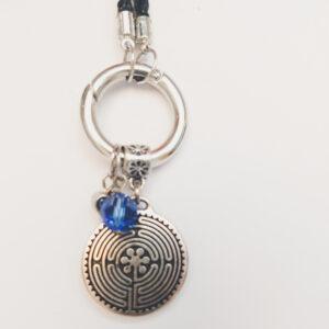 Ketting zwart leer clip-ring labyrint swarovski blauw. Zwarte gevlochten leren ketting met een metalen clip-ring met een bedel van een labyrint en van een hartje met een oneindige knoop erop met een blauwe swarovski kraal. De leren ketting is 76 cm lang.
