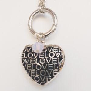 """Ketting ring hart swarovski roze. Metalen schakelketting met een metalen ring met bedel van een groot hart met het woord """"Love"""" erop. Er hangt een swarovski kraal aan in de kleur rose water opal, een roze kleur. De schakel ketting is 60 cm lang."""