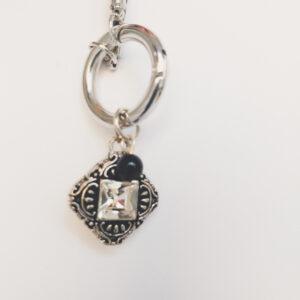Ketting grijs leer clip-ring romantic square swarovski kristal. Grijze gevlochten leren ketting met een metalen clip-ring met een vierkante bedel met een vierkante swarovski steen in de kleur crystal, een kristal kleur. Er hangt een zwarte swarovski parel aan. De leren ketting is 76 cm lang.