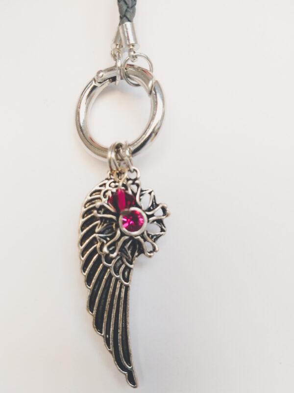 Ketting grijs leer clip-ring vleugel swarovski donker roze. Grijze gevlochten leren ketting met een metalen clip-ring met een bedel van een vleugel en een bloem met een swarovski steentje. Er hangt een swarovski kraal aan in de kleur fuchsia, een donker roze kleur. De leren ketting is 76 cm lang.