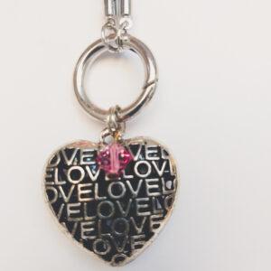 """Ketting grijs leer clip-ring hart swarovski roze. Grijze gevlochten leren ketting met een metalen clip-ring met een bedel van een hart met het woord """"LOVE"""" erop. Er hangt een swarovski kraal aan in de kleur rose, een roze kleur. De leren ketting is 76 cm lang."""