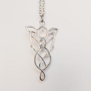 Ketting fairy tale kristal. Een dun metalen kettinkje met een metalen hanger eraan in een art noveau stijl met in het midden een glas steentje in de kleur kristal. Het kettinkje is 50 cm lang.