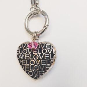 """Ketting zwart leer clip-ring hart swarovski roze. Zwarte gevlochten leren ketting met een metalen clip-ring met een bedel van een hart met het woord """"Love"""" erop. Er hangt een swarovski kraal aan in de kleur rose, een roze kleur. De leren ketting is 76 cm lang."""