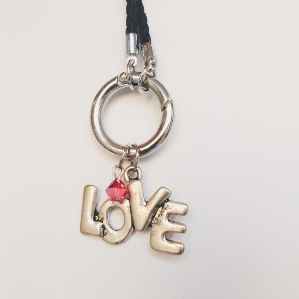 """Ketting zwart leer clip-ring love glas rood. Zwarte gevlochten leren ketting met een metalen clip-ring met een bedel van het woord """"Love"""". Met een facet geslepen rood glas kraaltje. De leren ketting is 76 cm lang."""
