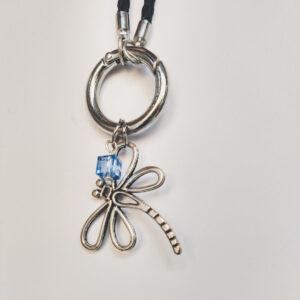 Ketting zwart leer clip-ring libelle glas blauw. Zwarte gevlochten leren ketting met een metalen clip-ring met een bedel van een libelle. Met een facet geslepen blauw vierkant glas kraaltje. De leren ketting is 76 cm lang.