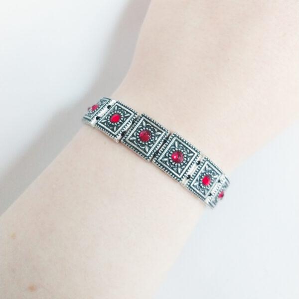 Armband romantic square swarovski rood. Armband met metalen vierkante kastjes met swarovski steentjes in de kleur siam, een rode kleur. De armband wordt getoond om de pols van blanke vrouw.
