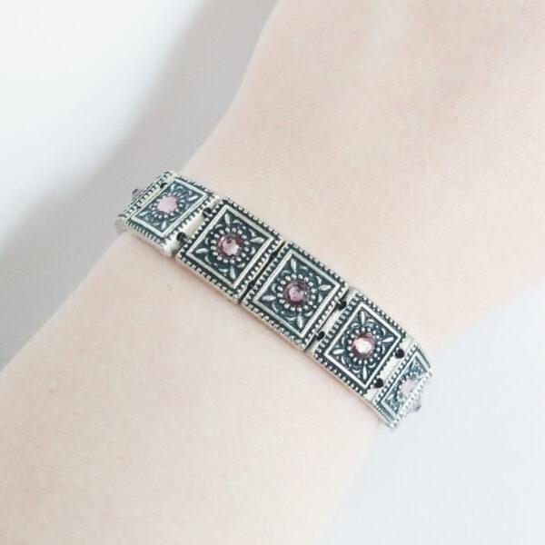 Armband romantic square swarovski oud roze. Armband met metalen vierkante kastjes met swarovski steentjes in de kleur antique pink, een oud roze kleur. De armband wordt getoond om de pols van een blanke vrouw.