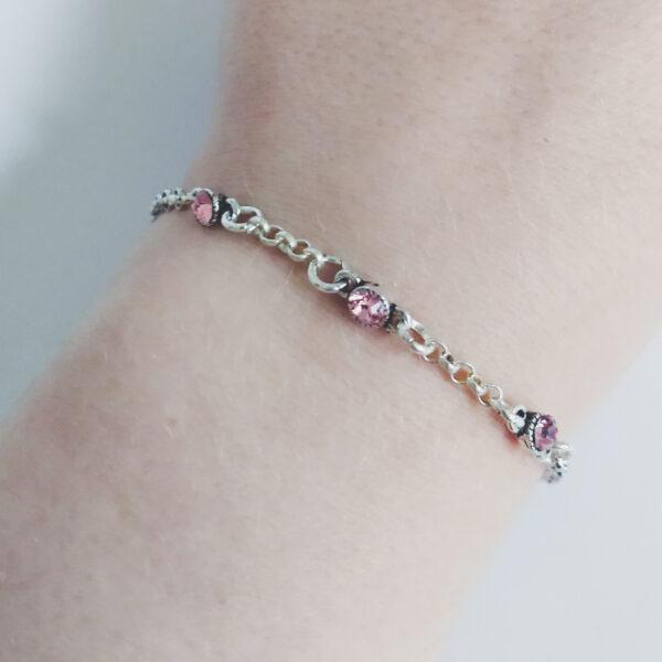 Fijne armband swarovski roze. Armband met kleine schakels van jasseron met 3 kleine swarovski steentjes in de kleur light rose, een roze kleur. Bij het slotje hangt een bedeltje in de vorm van een roos. De armband wordt getoond om de pols van een blanke vrouw.