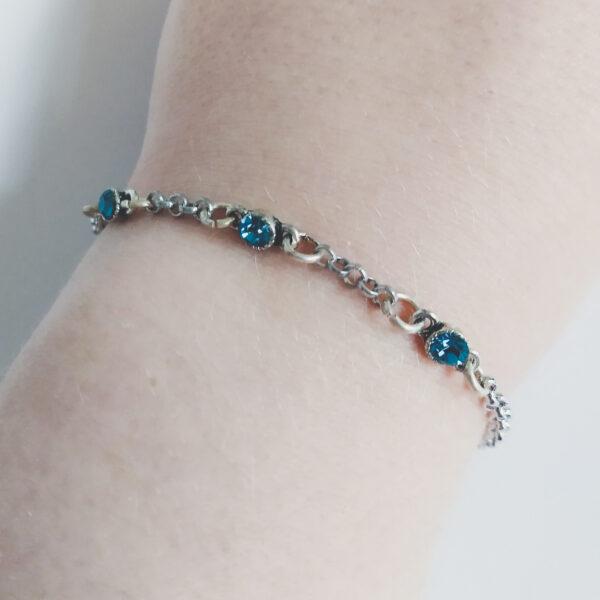 Fijne armband swarovski blauw groen. Armband met kleine schakels van jasseron met 3 kleine swarovski steentjes in de kleur indicolite, een blauw groene kleur. Bij het slotje hangt een bedeltje in de vorm van een vogel. Armband wordt getoond om de pols van een blanke vrouw.