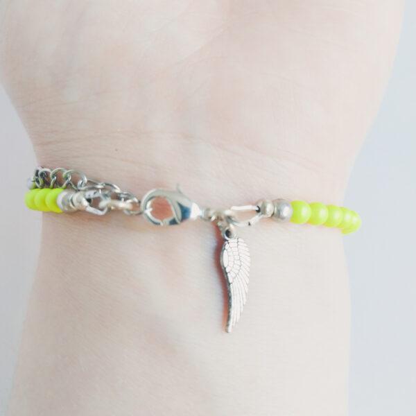 Armband swarovski parel neon geel. Een armband met kleine 4 mm swarovski pareltjes in een neon gele kleur. Met een metalen bedeltje in de vorm van een vleugel. De onderkant van de armband wordt getoond om de pols van een blanke vrouw.