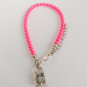 Armband swarovski parel neon roze. Een armband met kleine 4 mm swarovski pareltjes in een neon roze kleur. Bij het slotje hangt een bedeltje in de vorm van een slotje met een hart erop.