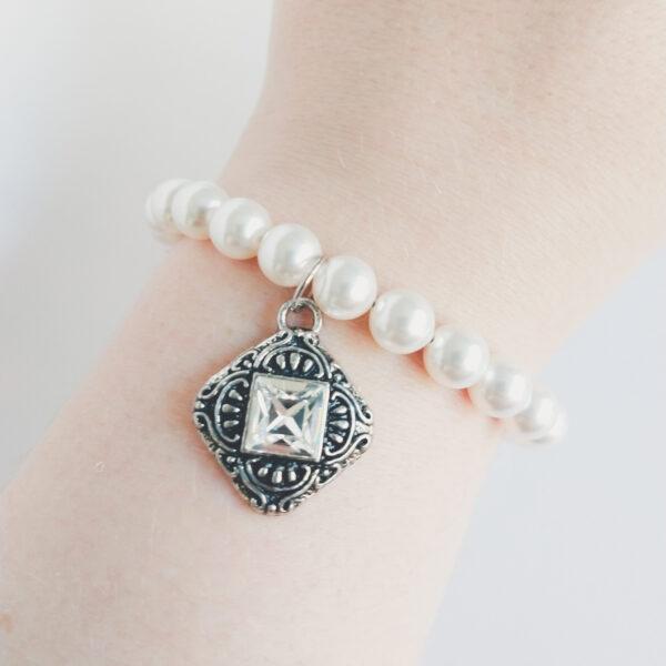 Armband romantic square swarovski parel wit. Armband met 8 mm swarovski parels in een witte kleur. Met een vierkant metalen bedel met een vierkante swarovski steen in de kleur cyrstal (kristal). De armband wordt getoond om de pols van een blanke vrouw.