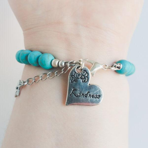 """Armband natuursteen turquoise. Armband met 8 mm natuursteen turquoise kralen. Met een hart vormige metalen bedel bij het slotje met een willekeurige tekst erop. (Bijvoorbeeld """"Kindness"""" of """"Joy"""") Er zit een verlengkettinkje aan zodat de armband verstelbaar is tot verschillende maten. Aan het einde van het verlengkettinkje hangt nog een klein metalen sterretje. De onderkant van de armband wordt getoond om de pols van een blanke vrouw."""