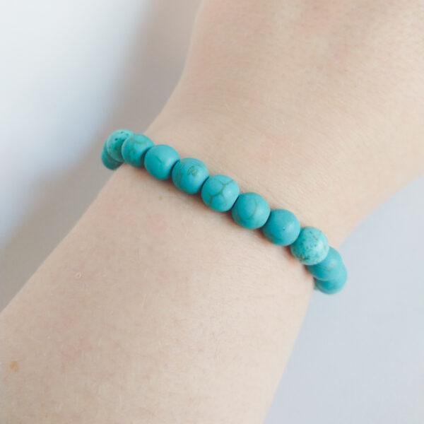 Armband natuursteen turquoise. Armband met 8 mm natuursteen turquoise kralen. De armband wordt getoond om de pols van een blanke vrouw.
