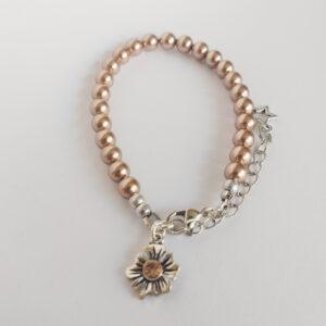 Armband swarovski parel 6 mm koper. Een armband met 6 mm swarovski parels in een koper kleur. Bij het slotje hangt een bedeltje in de vorm van een bloem met een swarovski steentje erin in de kleur peach.