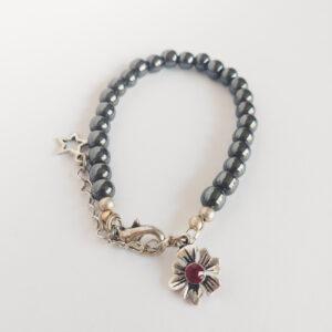 Armband swarovski parel 6 mm donker grijs. Een armband met 6 mm swarovski parels in een donker grijze kleur. Bij het slotje hangt een bedeltje in de vorm van een bloem met een swarovski steentje erin in de kleur rood.