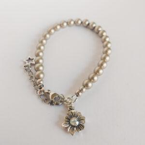 Armband swarovski parel 6 mm platinum. Een armband met 6 mm swarovski parels in een platinum kleur. Bij het slotje hangt een bedeltje in de vorm van een bloem met een swarovski steentje erin in de kleur kristal.