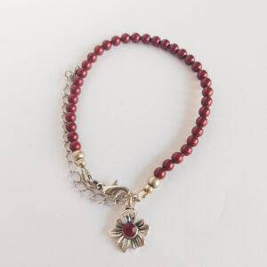 Armband swarovski parel 4 mm rood. Een armband met 4 mm swarovski pareltjes in een rode kleur. Bij het slotje hangt een bedeltje in de vorm van een bloem met een swarovski steentje erin in de kleur siam, een rode kleur.