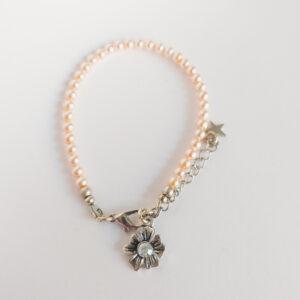 Armband swarovski parel 4 mm zalm roze. Een armband met 4 mm swarovski pareltjes in een zalm roze kleur. Bij het slotje hangt een bedeltje in de vorm van een bloem met een swarovski steentje erin in de kleur opal white, een melk witte kleur.