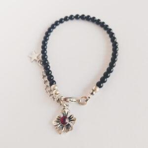 Armband swarovski parel 4 mm zwart. Een armband met 4 mm swarovski pareltjes in een zwarte kleur. Bij het slotje hangt een bedeltje in de vorm van een bloem met een swarovski steentje erin in de kleur siam, een rode kleur.