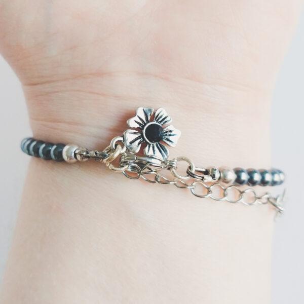 Armband swarovski parel 4 mm grijs. Een armband met kleine 4 mm swarovski pareltjes in een grijze kleur. Met een metalen bedeltje in de vorm van een bloem met een jet (zwart) swarovski steentje. De onderkant van de armband wordt getoond om de pols van een blanke vrouw.