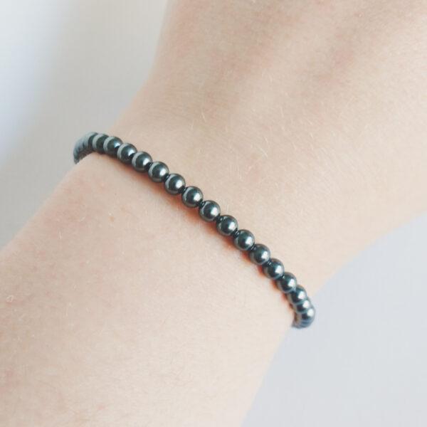 Armband swarovski parel 4 mm grijs. Een armband met kleine 4 mm swarovski pareltjes in een grijze kleur. De armband wordt getoond om de pols van een blanke vrouw.