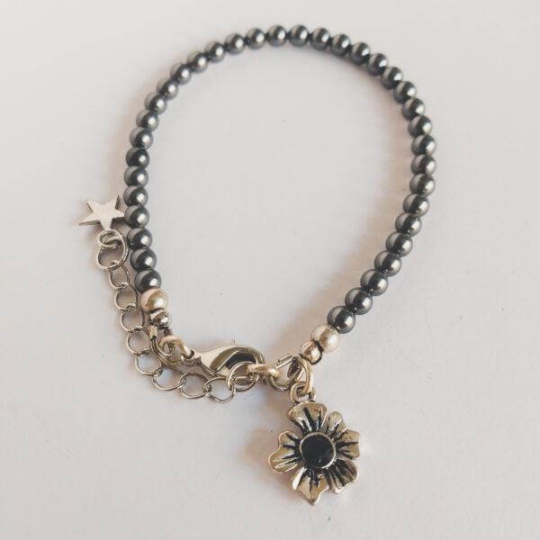 Armband swarovski parel 4 mm grijs. Een armband met 4 mm swarovski pareltjes in een grijze kleur. Bij het slotje hangt een bedeltje in de vorm van een bloem met een swarovski steentje erin in de kleur jet, een zwarte kleur.