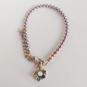 Armband swarovski parel 4 mm paars. Een armband met 4 mm swarovski pareltjes in een paarse kleur. Bij het slotje hangt een bedeltje in de vorm van een bloem met een swarovski steentje erin in de kleur opal white, een melk witte kleur.